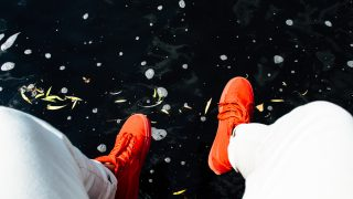 オレンジ色の靴を履く人の足元