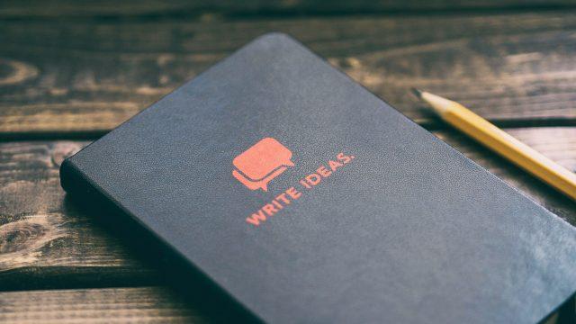 アイデアをメモするノートとペン