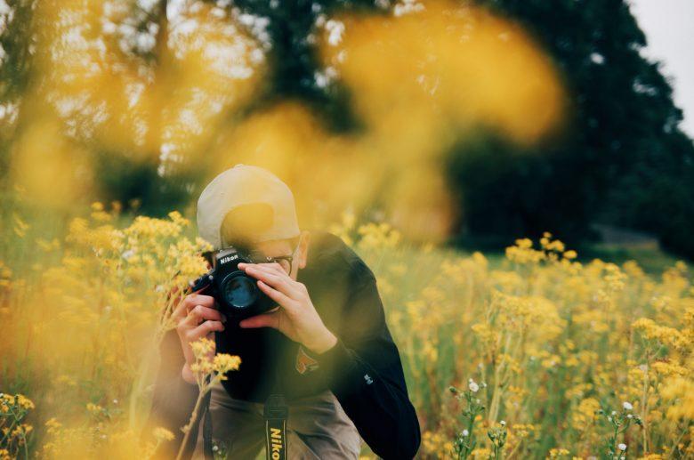 花畑でこちらにカメラを向ける男性