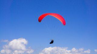 赤いパラグライダーで空を飛ぶ人