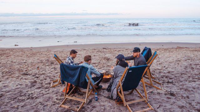 海岸で焚き火をする四人組
