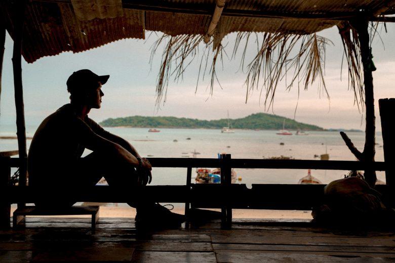 浜辺の小屋のベンチに座る男性