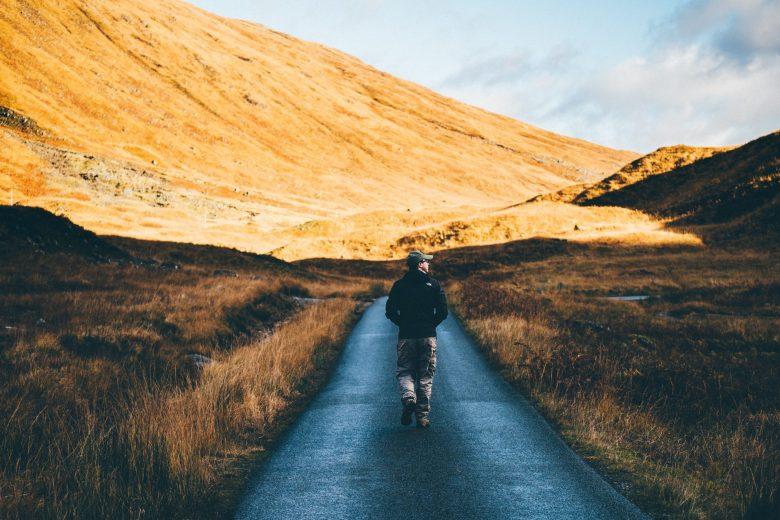 まっすぐな山道を進む男性