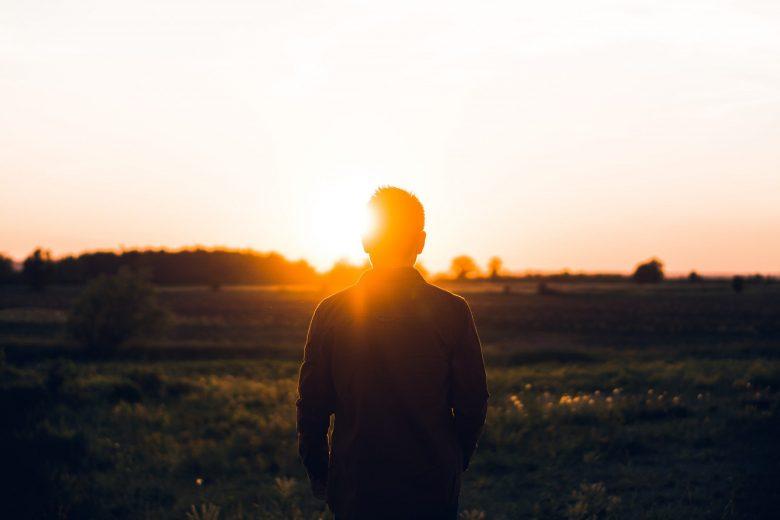 朝日を眺める男性の後ろ姿