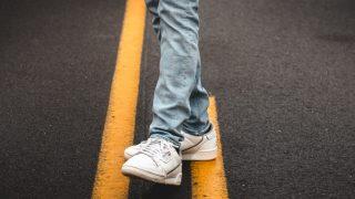 ブルーデニムと白いスニーカーを履いて道路を歩く人